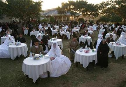 Iraqi newlyweds sit at a mass wedding ceremony involving 200 couples organized by the local government in Hilla, 100 km (62 miles) south of Baghdad December 1, 2008. REUTERS/Mushtaq Muhammed