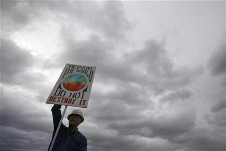 A demonstrator holds a placard at Camp for Climate Change's protest site at Blackheath in south London August 26, 2009. REUTERS/Stefan Wermuth