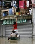"""<p>Жители с каноэ закупают продовольствие в магазине, который оказался затопленным из-за урагана """"Кетсана"""", лагуна Бинан 29 сентября 2009 года. Число жертв урагана """"Кетсана"""", обрушившегося на Филиппины в прошлый уик-энд, достигло 240 человек. REUTERS/Erik de Castro</p>"""
