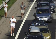 <p>Люди бегут вдоль 9-километровой пробки в Аироло, Швейцария 15 августа 2009 года. Может, экономический кризис и бьет по кошельку, зато ведет к оздоровлению жителей планеты, свидетельствуют данные исследования ученых университета Мичигана. REUTERS/Fiorenzo Maffi</p>