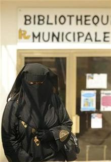 A woman wears a burqa as she walks up the stairs outside the municipal library in Ronchin northern France on August 9, 2009. REUTERS/Farid Alouache