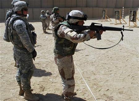 U.S. Army Sgt. Cody Rome (L), of Baton Rouge, LA, gives pointers to an Iraqi Soldier as he conducts a reflexive live-fire qualification exercise, at Combat Outpost Carver, Iraq, located outside of southeastern Baghdad, September 9, 2009. Picture taken September 9, 2009. REUTERS/U.S. Army/Pvt. Jared Gehmann/Handout