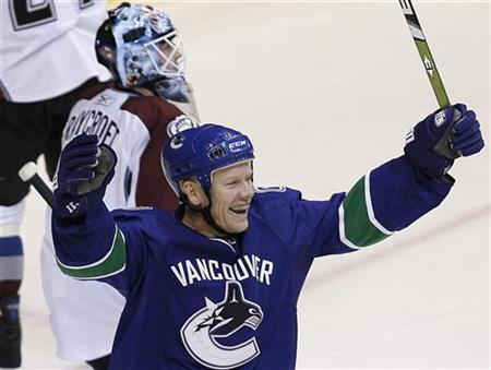 Vancouver Canucks' Mats Sundin (front) celebrates a goal against Colorado Avalanche's Andrew Raycroft by team-mate Alexander Edler (not shown) during the third period of NHL action in Vancouver, British Columbia March 15, 2009. REUTERS/Lyle Stafford