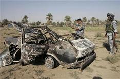 <p>Iraqi policemen examine the car that was used in an attack at an Iraqi checkpoint in southwest Baghdad's Amil district September 29, 2009. REUTERS/Bassim Shati</p>