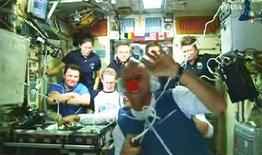 """<p>Il """"clown"""" miliardario Guy Laliberte (in primo piano) saluta durante una video-conferenza dalla stazione spaziale internazionale. REUTERS/NASA TV</p>"""