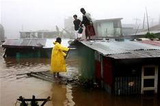 <p>Житель Багио на самодельном плоту пытается спастись сам и спасти своих соседей после того, как их дома затопило из-за непрекращающихся дождей 4 октября 2009 года. Разрушительный тайфун, бушевавший на выходных на севере Филиппин, покидая пределы страны, столкнулся над Тихим океаном с новым циклоном. Теперь оба шторма готовятся с новой силой обрушиться на затопленные Филиппины. REUTERS/Stringer</p>
