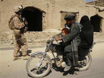 An Afghani family on a motorcycle passes by U.S. Marine SGT Peter Neubauer, from 8th Marine Regiment, as he walks during a foot patrol in Garmsir district in Helmand province, October 5, 2009. REUTERS/Asmaa Waguih