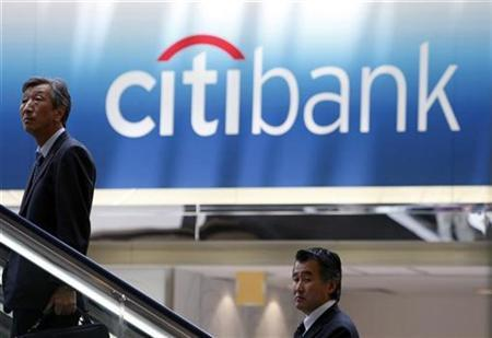 Men travel on an escalator near a Citibank signboard in Tokyo June 26, 2009. REUTERS/Kim Kyung-Hoon