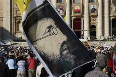 <p>A pilgrim holds a flag showing Belgian missionary Father Damien as Pope Benedict leads a canonisation mass at St. Peter's Basilica in the Vatican, October 11, 2009. REUTERS/Francois Lenoir</p>