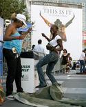 """<p>Mulheres dançam diante de cartaz promocional de Michael Jackson em Los Angeles. Horas depois do lançamento do primeiro single póstumo de Michael Jackson, """"This Is It"""", em meio a uma grande expectativa na segunda-feira, surgiu a informação de que a faixa foi gravada 18 anos atrás por um cantor porto-riquenho.25/09/2009.REUTERS/Danny Moloshok</p>"""