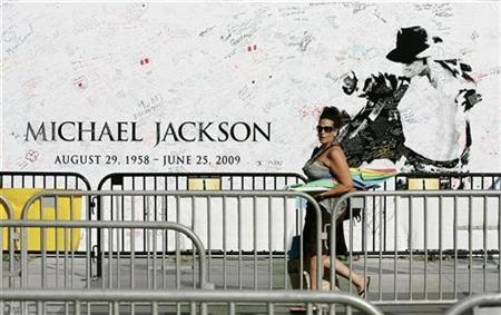 A woman walks past a memorial banner that fans have signed at the L.A. Live complex for the opportunity to purchase tickets for a special showing of the ''Michael Jackson's This Is It'' movie in Los Angeles, September 25, 2009. REUTERS/Danny Moloshok