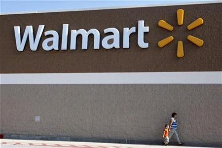 People walk past a Wal-Mart sign in Rogers, Arkansas in this June 4, 2009 file photo. Walmart.com wants to be the first place U.S. consumers go to when making an online purchase, and its announcement on Tuesday that it will sell health and beauty products will help it reach that goal, its chief executive officer said in an interview. REUTERS/Jessica Rinaldi