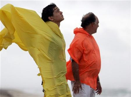 Men fight the wind and rain from tropical storm Ernesto in Miami, August 29, 2006. REUTERS/Marc Serota