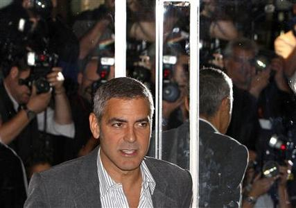 Photographers are reflected in a mirrored door as U.S. actor George Clooney arrives to speak about his new film ''Fantastic Mr. Fox'' in London, October 14, 2009. REUTERS/Luke MacGregor