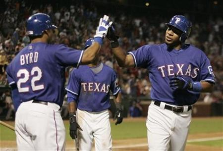 Texas Rangers Elvis Andrus (R) slaps hands with Rangers teammate Marlon Byrd (L) after hitting a two run home run against the Toronto Blue Jays during the fifth inning of American League MLB baseball action in Arlington, Texas September 2, 2009. REUTERS/Jessica Rinaldi