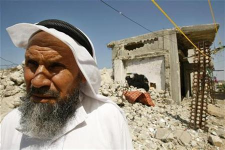 A Palestinian man walks past a house, damaged during the three-week offensive Israel launched last December, in Khan Younis in the southern Gaza Strip September 16, 2009. REUTERS/Ibraheem Abu Mustafa