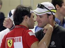 <p>O piloto Rubens Barrichello cumprimenta Felipe Massa, em Interlagos. Decepção. Foi assim que Rubens Barrichello descreveu o oitavo lugar com que terminou o Grande Prêmio do Brasil neste domingo e o fim da luta pelo título do campeonato de Fórmula 1.18/10/2009.REUTERS/Bruno Domingos</p>