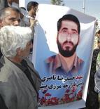 <p>Мужчина держит в руках портрет Хамида Насери - высокопоставленного офицера Корпуса стражей исламской революции Ирана, убитого при взрыве на востоке страны. Более сорока человек погибли в воскресенье на юге-востоке Ирана, когда экстремист-смертник привел в действие взрывное устройство рядом с Корпусом стражей исламской революции. REUTERS/ISNA</p>