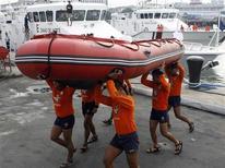 """<p>Филиппинская береговая охрана, готовясь к тайфуну """"Лупит"""", несет резиновую лодку, Манила 20 октября 2009 года. Тысячи жителей Филиппин эвакуируются из северных районов страны, опасаясь мощного тайфуна, грозящего островам новыми наводнениями и оползнями, сообщили власти страны. REUTERS/Romeo Ranoco</p>"""