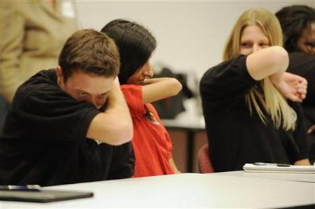 People practice coughing into their sleeves as a way to try to control the spread of the H1N1 swine flu virus, during a meeting for workers at the Maryland Department of Health and Mental Hygiene in Baltimore, September 3, 2009. REUTERS/Jonathan Ernst (UNITED STATES HEALTH)