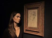 <p>An employee poses for photographers at the unveiling of Renaissance painter Raphael's fresco 'Head of a Muse' at Christie's auction house in London October 20, 2009. REUTERS/Kieran Doherty</p>