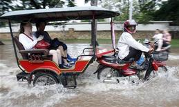 <p>Туристы перемещаются по затопленным улицам Сием Рипа 1 октября 2009 года. ВымпелКом решил продавать карточки оплаты за мобильную связь в Камбодже в брендированных тук-туках, передвигающихся по столице Пномпеню. REUTERS/Chor Sokunthea</p>