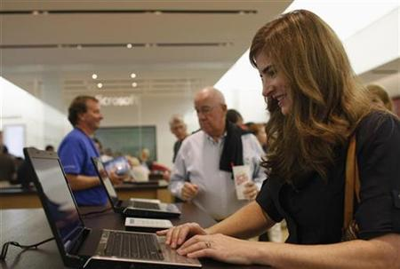 Kristin May (R) tries out a computer during the grand opening of Microsoft's first retail store in Scottsdale, Arizona October 22, 2009. REUTERS/Joshua Lott