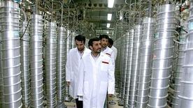 <p>Президент Ирана Махмуд Ахмадинежад (в центре) во время посещения предприятия по обогащению урана в Натанце8 апреля 2008 года. Секретные службы полагают, что Ирану потребуется не менее 18 месяцев для разработки ядерного оружия, если он все-таки решит создать его, сообщили западные дипломаты и представители спецслужб. REUTERS/Presidential official website/Handout</p>