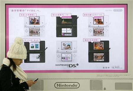 A woman uses her mobile phone in front of an electronic advertisement board of Japanese video game maker Nintendo Co. Ltd.'s handheld DSi game console at a train station in Tokyo February 1, 2009. REUTERS/Stringer