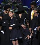 <p>I figli di Michael Jackson abbracciano gli zii durante la cerimonia funebre. REUTERS/Mark J. Terrill/Pool</p>