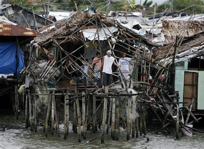 Residents living in Manila Bay look out from their house that was damaged by Typhoon Mirinae in Bacoor town, south of Manila, October 31, 2009. REUTERS/Erik de Castro