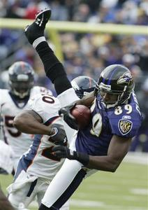 Baltimore Ravens wide receiver Mark Clayton (89) gets knocked to the ground by Denver Broncos safety Brian Dawkins during the second quarter of their NFL football game in Baltimore, Maryland, November 1, 2009. REUTERS/Joe Giza