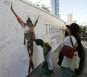 """<p>Mulher assinando em mural com cartaz do filme """"This is It"""" em homenagem a Michael Jackson em Los Angeles. O muito aguardado filme de shows de Michael Jackson reinou nas bilheterias do mundo todo neste domingo. Contudo, seu desempenho na América do Norte esteve longe de ser estelar. REUTERS/Danny Moloshok</p>"""
