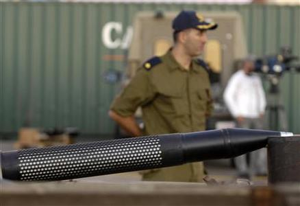 An Israeli naval officer stands near munitions displayed at the port of Ashdod November 4, 2009, that according to the military was found on the Antigua-flagged Francop vessel, intercepted overnight in the Mediterranean Sea, 100 miles (160 km) from Israel. REUTERS/Amir Cohen
