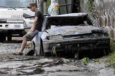 <p>A Salvadoran sits on a car damaged by heavy rains in San Salvador November 8, 2009. REUTERS/William Bonilla</p>