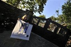 <p>Michael Jackson fan Veronica Garcia holds banner with a picture of Michael Jackson at the front gate of Neverland in Los Olivos, California on June 25, 2009. REUTERS/Phil Klein</p>