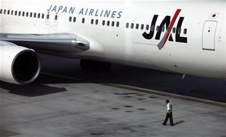 A worker walks past a Japan Airlines plane before takeoff at the Taoyuan International Airport October 30, 2009. REUTERS/Nicky Loh