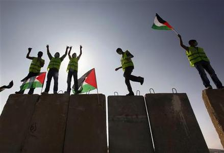 Palestinian and international activists stand atop a concrete blast wall on a patrol road used by Israeli troops along the controversial Israeli barrier during a protest marking the 20th anniversary of the toppling of the Berlin Wall, in the al-Amari refugee camp in the West Bank city of Ramallah, November 9, 2009. REUTERS/Yannis Behrakis