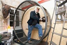 """<p>L'architetto francese Frederic Tabary fotografato dentro una """"ruota per criceti"""", in una delle stanze del suo particolare hotel. REUTERS/Stephane Mahe</p>"""
