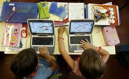 <p>Due scolarette seguono una lezione con il loro computer. REUTERS/Nacho Doce</p>