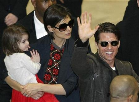 Actor Tom Cruise (R) waves to fans upon his arrival with his wife Katie Holmes (C) and their daughter Suri at Narita International Airport March 8, 2009. REUTERS/Issei Kato