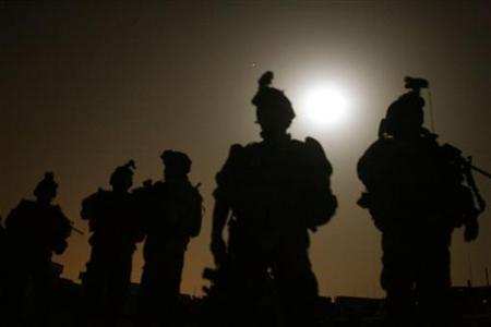 U.S. soldiers stand in front of a base before they start a night mission in Baquba early June 28 , 2007. REUTERS/Goran Tomasevic