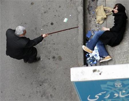 A man with a cane gestures towards a woman on the ground during protests in central Tehran June 14, 2009. REUTERS/Stringer
