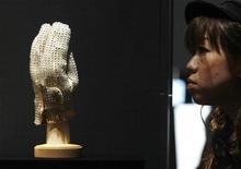 <p>Una donna osserva il guanto che Jackson indossava quando ha eseguito per la prima volta il Moonwalk. REUTERS/Yuriko Nakao (JAPAN ENTERTAINMENT)</p>