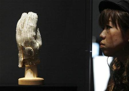 A woman looks at a sequined glove that once belonged to the late pop star at the MJ46 Japan Tour, an exhibition showcasing various Michael Jackson items, in Tokyo November 9, 2009. REUTERS/Yuriko Nakao