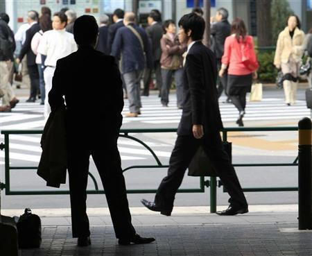 A man is silhouetted at a shopping district in Tokyo November 20, 2009. REUTERS/Kim Kyung-Hoon