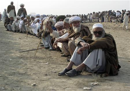 Men, fleeing a military offensive in South Waziristan, line up in a queue while waiting for their turn to collect handouts at a distribution point for internally displaced people (IDPs) in Dera Ismail Khan, located in Pakistan's restive North West Frontier Province, November 22, 2009. REUTERS/Mustansar Baloch