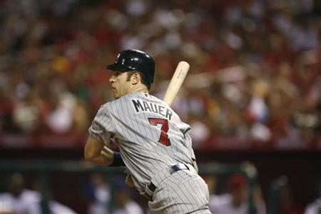 Minnesota Twins' Joe Mauer hits a RBI double in the fifth inning scoring New York Yankees' Derek Jeter for the American League's third run of Major League Baseball's All-Star game in St. Louis in this July 14, 2009 file photo. REUTERS/John Gress