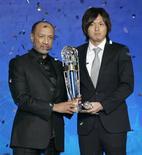 <p>O apoiador japonês Yasuhito Endo recebe o prêmio de melhor jogador do ano da Confederação Asiática de Futebol de seu presidente, Mohamed Bin Mammam, em Kuala Lumpur. REUTERS/Bazuki Muhammad</p>