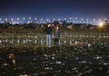 <p>Two people walk through the litter strewn muddy field in front of the 'Other' stage in the early hours of the morning at the end of Glastonbury Festival 2009 in south west England June 29, 2009. REUTERS/Luke MacGregor</p>